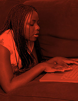 girl typing on laptop, red