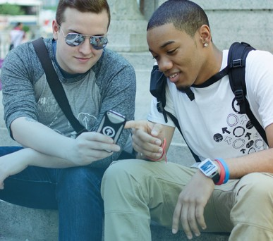 two boys wearing ATI apparel and looking at phone with ATI case